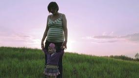 Den gravida modern och den lilla dottern dansar på en grön äng på en bakgrund av den scharlakansröda solnedgången lager videofilmer