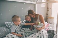 Den gravida modern och två söner läser en intressant bok hemma i morgonen Tillfällig livsstil i sovrum arkivbild