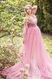 Den gravida unga härliga kvinnan i rosa färger snör åt den långa klänningen i en blomningträdgård Arkivfoton