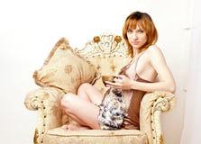 Den gravida unga kvinnan i en forntida stol med en kupa av tea Royaltyfri Bild