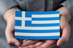Den grekiska flaggan gömma i handflatan in Arkivfoto