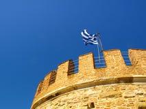 Den grekiska flaggan på det vita tornet av Thessaloniki på kusten av det Aegean havet, Thessaloniki, Grekland Arkivbilder