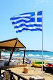 Den grekiska flaggan på stranden Royaltyfri Bild