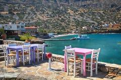 Den grekiska krogen med rosa färger och lilatabeller och vit presiderar overloo Royaltyfri Foto