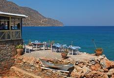 Den grekiska krogen med tabeller och stolar vaggar på kusten som förbiser mig Royaltyfri Fotografi