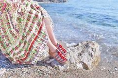 Den grekiska modellen annonserar bohemiska sandaler och kläder på stranden arkivbilder