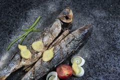 Den grillade fisken med kryddor, grönsaker och örter kritiserar på bakgrund som är klar för att äta arkivfoto