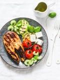 Den grillade laxen, zucchini, bakade körsbärsröda tomater och fetaost - sunt allsidigt mål på ljus bakgrund arkivfoton