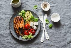 Den grillade laxen, zucchini, bakade körsbärsröda tomater och den silkeslena tofuen - sunt allsidigt mål på grå bakgrund royaltyfri foto