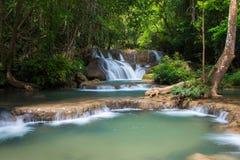 Den gröna vattenfallet i djup skog, den Erawan vattenfallet lokaliserade Kanchanaburi Fotografering för Bildbyråer