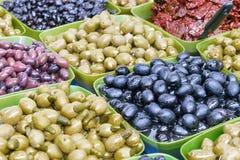 In den großen Schüsseln ausgebreitete Oliven von verschiedenen Farben Stockfoto