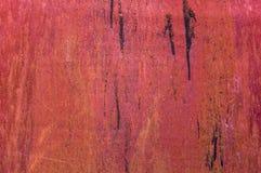Den grova metallväggen med tjära spårar främst rött med skrapor Arkivfoton