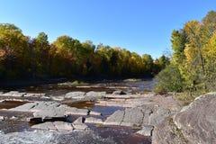 Den grunda rinnande vattenfallet fodrade med träd på en nedgångaftermoon arkivbilder
