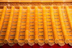 Den gula apelsinen glasade terrakottataktegelplattor av en kinesisk tempel Royaltyfri Bild