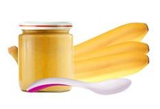 Den gula bananen och kruset av behandla som ett barn puré som isoleras på vit Fotografering för Bildbyråer