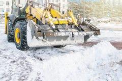 Den gula bulldozern gör klar gatan efter ett tungt naturligt snöfall Förbereda sig för jul Solig frostig dag Närbild arkivbilder