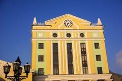 Den gula byggnaden med klockan på väggen Royaltyfri Fotografi