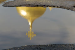 Den gula (guld-) kupolen av kyrkan med korset reflekteras Royaltyfri Bild