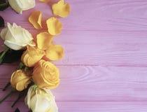 Den gula hälsningen för gruppen för romans för friskhetfödelsedagbuketten steg på en rosa träbakgrund, ram royaltyfri foto