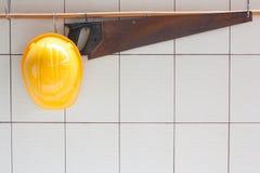 Den gula hårda hatten och handen såg att hänga på tegelplattaväggen Arkivfoton