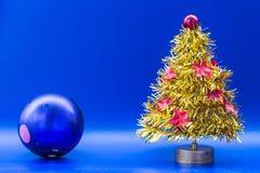 Den gula konstgjorda julgranen dekorerade med rött blänka a Royaltyfri Bild