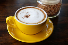Den gula koppen av cappuccino i den gula koppen och den glass kruset av socker på träbakgrunden Arkivbilder