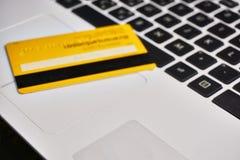 Den gula kreditkorten är den pålagda anteckningsboken Arkivfoto