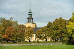 Den gula kyrkan som göras av stenen i höst, färgar arkivfoto
