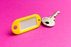 Den gula nyckel- etiketten på en lila texturerade pappbakgrund Begreppet av hyra som säljer mall trendfärger royaltyfria bilder