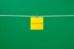 Den gula pappers- anmärkningen på klädstreck med text tackar dig Royaltyfria Foton