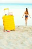 Den gula resväskan på stranden och en flicka går in i havet i th Royaltyfri Bild