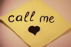 Den gula servetten på en tabell med en inskrift` kallar mig `, Arkivfoto