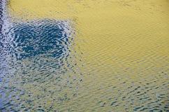 Den gula sjöboden reflekterade i sorlvatten för bakgrund Arkivbild