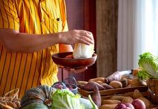 Den gula skjortakockmannen väljer ingrediensen och råvaran för hans kock av den dag vid valda olika grönsaker i hans kök arkivfoton
