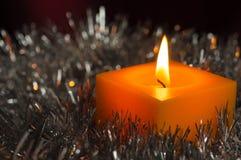 Den gula stearinljuset bland en silvrig dekor Fotografering för Bildbyråer