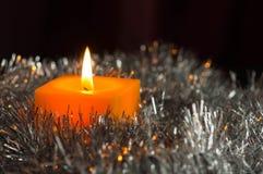 Den gula stearinljuset bränner bland en silvrig dekor Arkivfoton