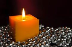 Den gula stearinljuset med en dekor från silver klumpa ihop sig Arkivbilder