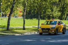 Den gula taxien rider på gatan i Moskva royaltyfri bild