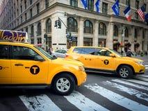 Den gula taxin rusar till och med den femte avenyn, New York City Arkivbilder