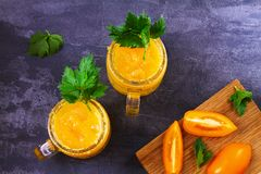 Den gula tomatcoctailen med selleri, kryddor, saltar och is Royaltyfri Foto