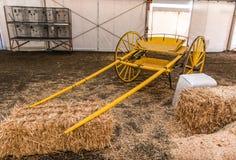 Den gula tomma vagnen sitter nära höbaler Royaltyfri Fotografi