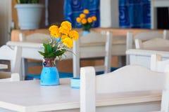 Den gula tusenskönan blommar i blå vas på en tabell på den grekiska krogen på Kretaön Arkivbilder