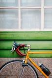 Den gula vägen cyklar parkering mot den gröna träväggen Arkivfoto