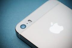 Den guld- Apple iPhonen 5s på bakgrund för blått papper Arkivfoton