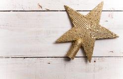 Den guld- blänka stjärnan formade julprydnaden på vitt trä Royaltyfri Bild