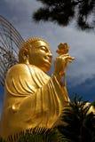 Den guld- Buddha som rymmer den guld- lotusblomman metar upp Royaltyfri Bild
