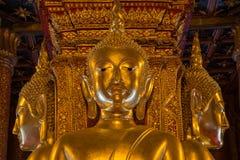Den guld- Buddhastatyn i kyrka av Wat Phumin arkivfoto