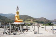 Den guld- Buddhastatyn vänder till berget i backgrounen Royaltyfri Fotografi