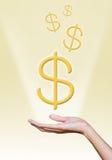 Den guld- dollaren undertecknar över handen Arkivfoton
