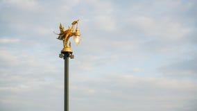 Den guld- fågellampstolpen på en himmelbakgrund Arkivbild